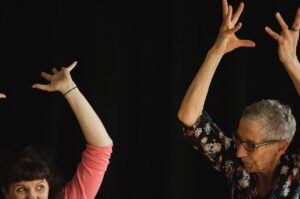 Two women with hands over head | Collective Identity